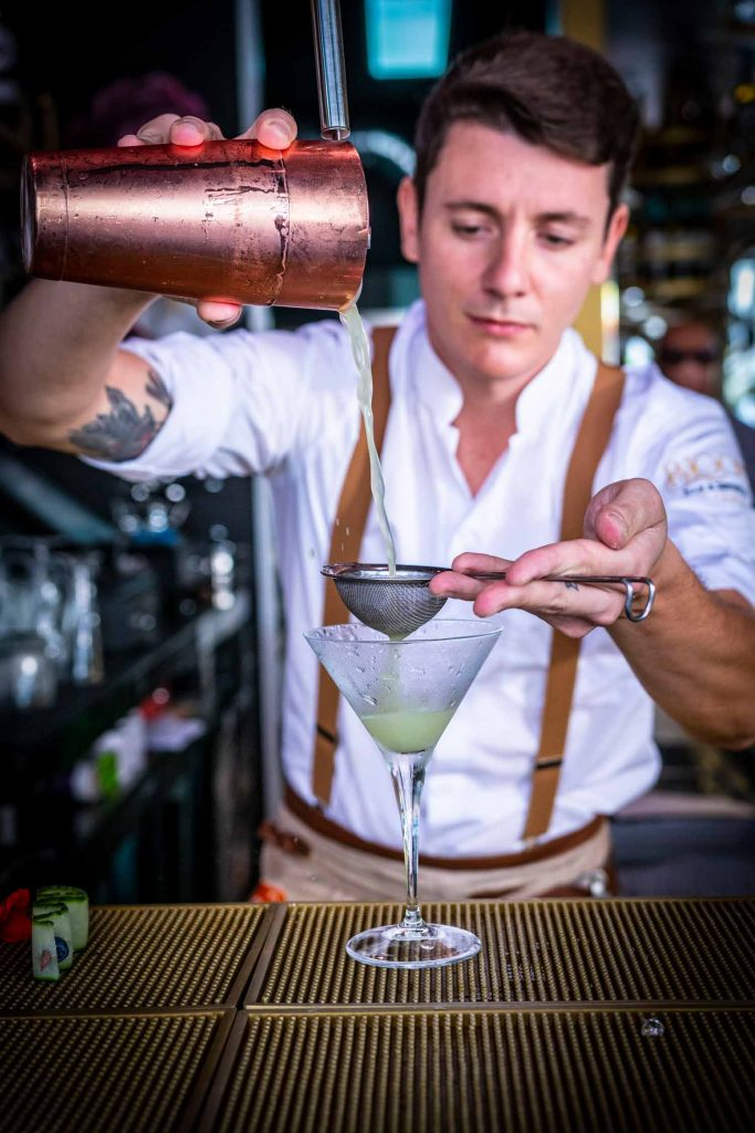 Bar staff adds signature 130 Blooms cocktail to martini glass.