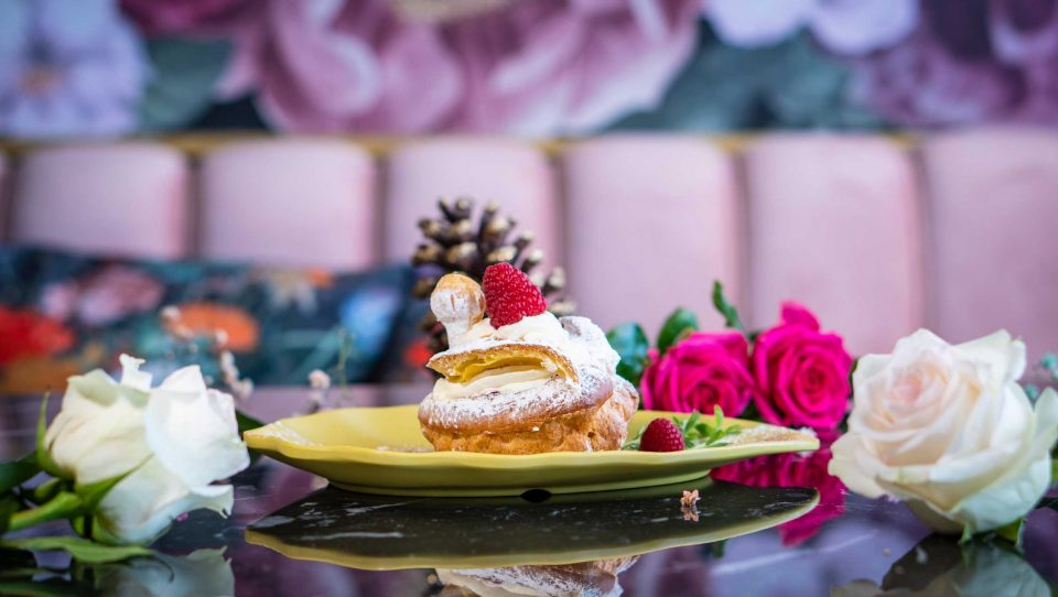 """The Swan,"" an elegant and indulgent Belgian pastry and dessert, served with cream and red berries."
