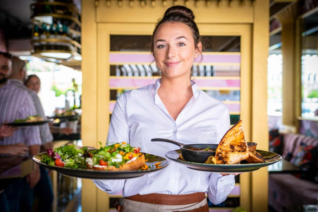 Waitress serving two Bloom brunch dishes - Poached Eggs & Avocado and Shakshuka Eggs