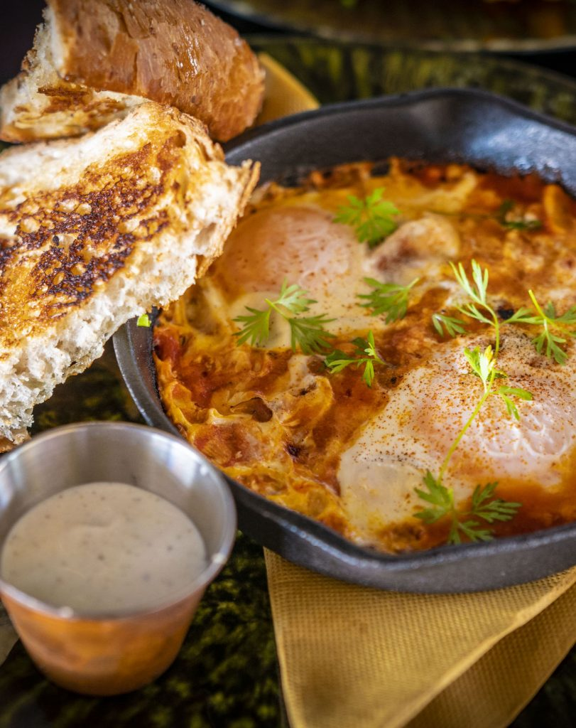 Shakshuka with poached eggs in pan, served with bread and yogurt.