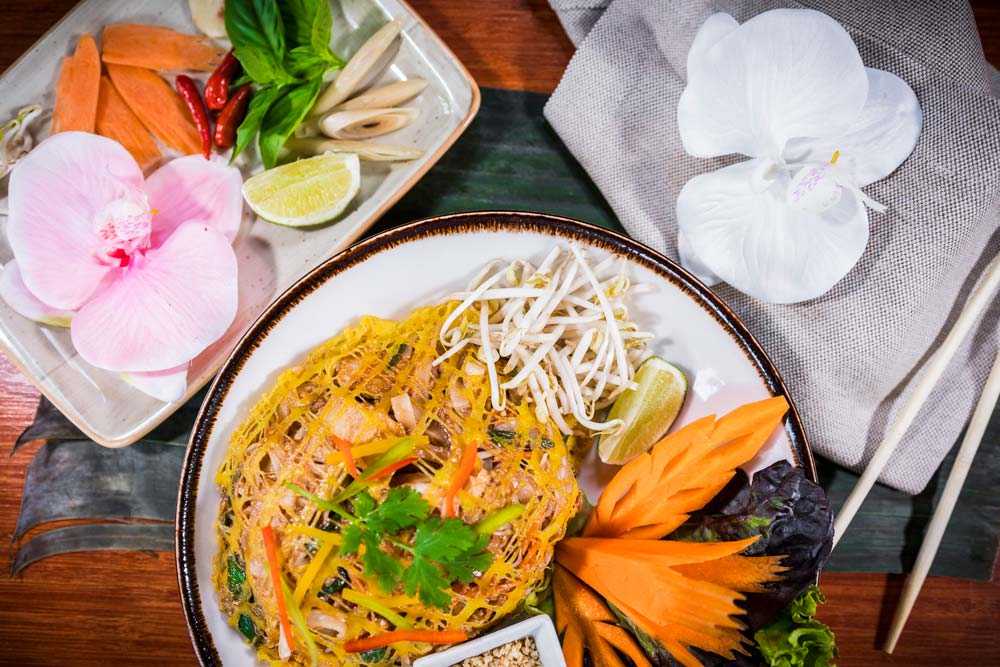Botanico Phad Thai with king prawns and diced chicken in omelette basket. Garnished with decorative vegetables.