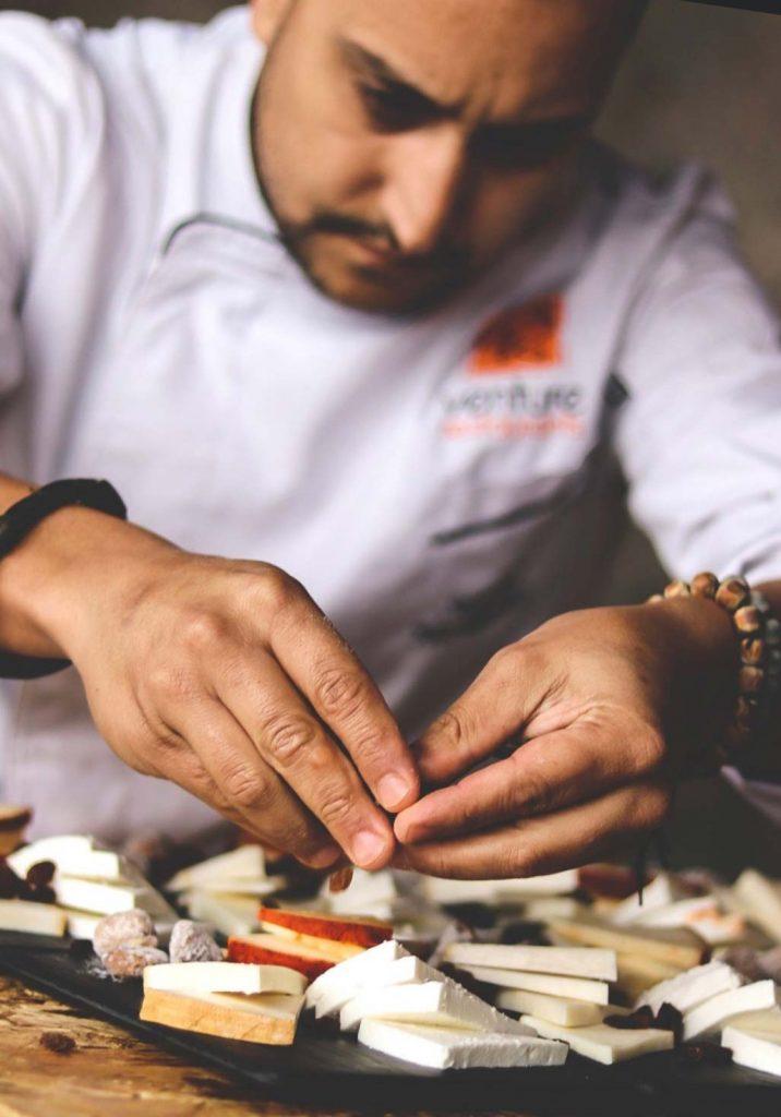 Chef preparing cheese board.